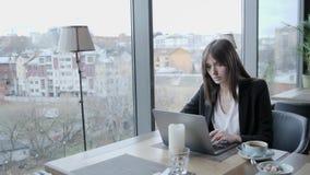 侵害和严重起反应 坐在咖啡馆的年轻女人在木桌上 在桌上是灰色铝膝上型计算机 影视素材