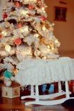 轻便小床在圣诞树下 免版税库存图片