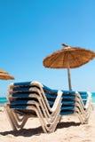轻便折叠躺椅和遮阳伞在海滩 免版税库存照片
