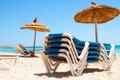 轻便折叠躺椅和遮阳伞在海滩 免版税图库摄影