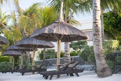 轻便折叠躺椅在一个热带海滩的一把伞下 免版税库存照片