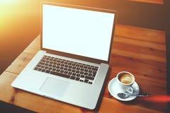 便携式的说谎在咖啡馆的一张木桌上的便携式计算机和咖啡禁止内部 免版税库存照片