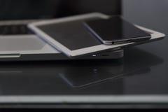 便携式计算机、数字式片剂和手机在黑桌上 免版税图库摄影