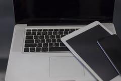 便携式计算机、数字式片剂和手机在黑桌上 库存图片