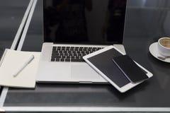 便携式计算机、数字式片剂和手机在黑桌上 免版税库存照片