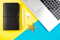 便携式计算机、旅行笔记本和贝壳和海星在蓝色和黄色背景 免版税图库摄影
