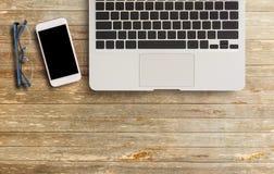 便携式计算机、玻璃和巧妙的电话在木桌上 库存照片