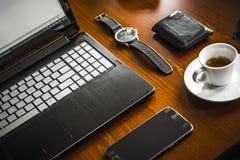 便携式计算机、coffe、手表、玻璃和钱包在木书桌上 免版税图库摄影