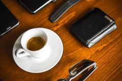 便携式计算机、coffe、手表、玻璃和钱包在木书桌上 库存照片
