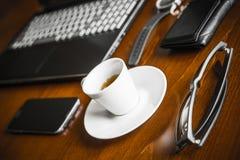 便携式计算机、coffe、手表、玻璃和钱包在木书桌上 免版税库存图片