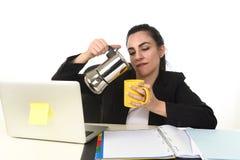 便携式计算机书桌饮用的咖啡的女商人激动和急切在咖啡因瘾 免版税库存图片