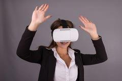 便携的技术VR玻璃的女商人 一套西装的确信的少妇在虚拟现实耳机 库存照片