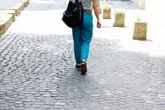 便服和背包的一年轻女人步行沿着向下街道 妇女从后面看 ?? 免版税库存照片