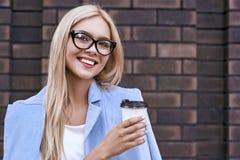 便服和镜片的美丽的年轻女人拿着一杯咖啡和微笑 库存图片