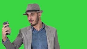 便服帽子行家stylerecording的vlog或打的视频通话在一个绿色屏幕上,色度钥匙可爱的人 股票录像
