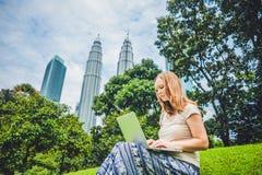 便服的一个少妇使用膝上型计算机在摩天大楼背景的一个热带公园  咖啡计算机概念杯子膝上型计算机映射移动下办公室文书工作被充塞 免版税图库摄影