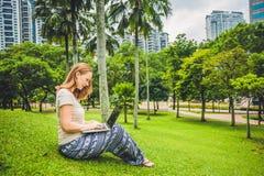 便服的一个少妇使用膝上型计算机在摩天大楼背景的一个热带公园  咖啡计算机概念杯子膝上型计算机映射移动下办公室文书工作被充塞 免版税库存照片