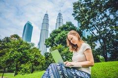 便服的一个少妇使用膝上型计算机在摩天大楼背景的一个热带公园  咖啡计算机概念杯子膝上型计算机映射移动下办公室文书工作被充塞 库存图片