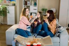 便服的在家吃在沙发的三个愉快的年轻女性朋友画象比萨 妇女友谊,吃 免版税库存图片