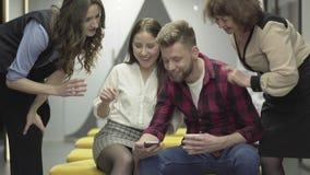 便服的年轻人在显示她的图片的俏丽的女性同事附近坐他的手机 他们邀请了 影视素材