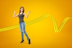 便服的年轻愉快的深色的女孩有在黄色背景的测量的磁带的 免版税库存照片