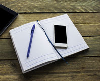 便条纸、铅笔、片剂和电话在老木书桌上 Simpl 免版税库存照片