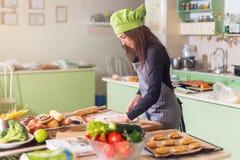 便衣、围裙和帽子辗压面团的少妇一个饼的在厨房里 做酥皮点心的女性面包师 免版税库存图片