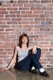 便衣、蓝色牛仔裤和背心灰色的可爱的少妇看照相机和微笑的坐地板 免版税图库摄影