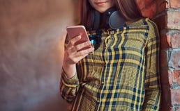 便衣听的音乐的年轻深色的学生女孩,当使用智能手机时,当倾斜反对砖时 库存照片