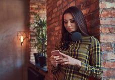 便衣听的音乐的年轻深色的学生女孩,当使用智能手机时,当倾斜反对砖时 免版税图库摄影
