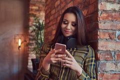 便衣听的音乐的年轻深色的学生女孩,当使用智能手机时,当倾斜反对砖时 库存图片