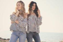 便衣摆在的两个美丽的女孩室外 免版税图库摄影