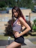 便衣的一个可爱的行家女孩坐都市背景 时尚,青年概念 免版税图库摄影