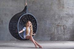 便衣的一个逗人喜爱的美丽的小女孩坐一把暂停的椅子在一个空的演播室 免版税库存照片