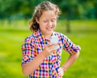 便衣的可爱的微笑的十几岁的女孩有智能手机的 库存图片