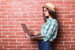 便衣的妇女使用一台膝上型计算机 库存图片
