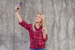 便衣的妇女有在她的愉快的微笑taling的selfie的 免版税库存图片