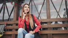 便衣的年轻美丽的女孩坐一条长凳在城市公园 股票录像