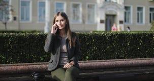便衣的年轻美丽的女孩坐长凳和谈话在手机 股票视频