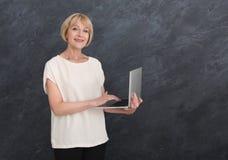 便衣的成熟妇女使用反对灰色背景的膝上型计算机 图库摄影