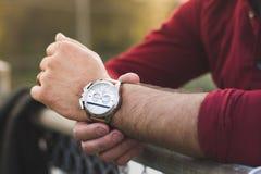便衣的检查花梢手表的年轻人特写镜头  免版税库存照片