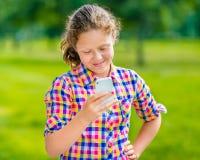 便衣的甜点微笑的十几岁的女孩有智能手机的 库存图片