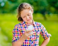 便衣的相当微笑的十几岁的女孩有智能手机的 图库摄影