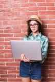 便衣的美丽的少妇使用一台膝上型计算机 免版税库存照片