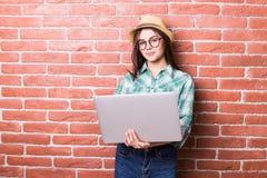 便衣的美丽的少妇使用一台膝上型计算机 库存照片