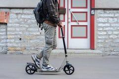 便衣的年轻人在街道上的反撞力滑行车 库存照片
