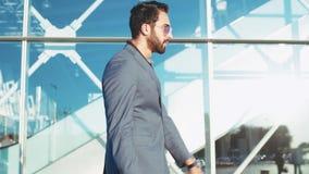 便衣的年轻有胡子的在拉扯手提箱的仓促的人和太阳镜对机场入口,检查时间 股票录像