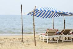 轻便马车休息室在海滩的一个机盖下在海洋附近 免版税库存图片