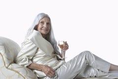 轻便马车休息室的典雅的资深妇女有香宾的 免版税库存图片