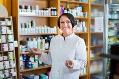 促进健康补充的白色外套的妇女在药房 库存照片